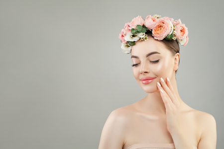 Beautiful face. Healthy woman with clear skin and flowers Reklamní fotografie - 124893966