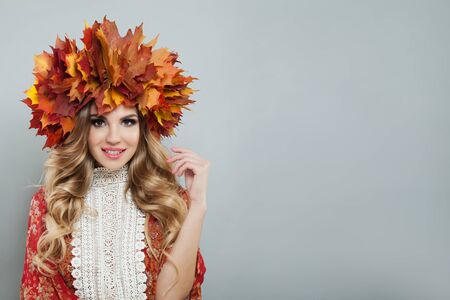 Happy smiling woman with makeup and long curly hair. Pretty model in autumn leaves crown Banco de Imagens