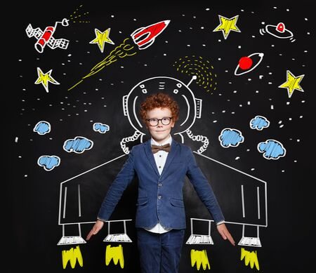 Child boy astronaut on blackboard background with space pattern
