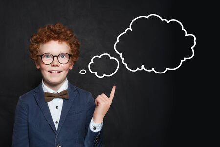 Smiling child and empty speech clouds bubbles on chalkboard background