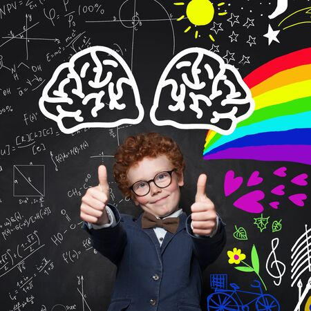 Smart kid withthumb up on chalkboard background with maths formula and art pattern. Creativity education concept