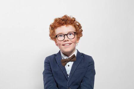 Netter rothaariger Junge mit Brille, der auf weißem Hintergrund nachschaut