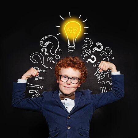 Strong child boy with lightbulb on blackboard background. Brainstorming and idea concept Reklamní fotografie