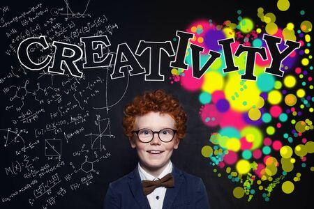 Creativity concept. Smart child student on blackboard background Reklamní fotografie