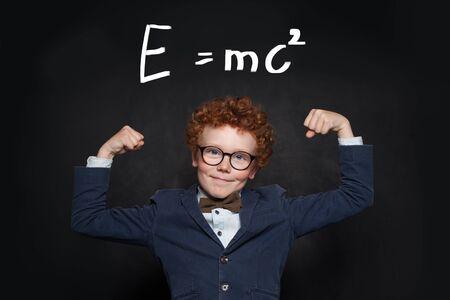 Starker und intelligenter Kinderstudent auf Tafel mit Wissenschaftsformel