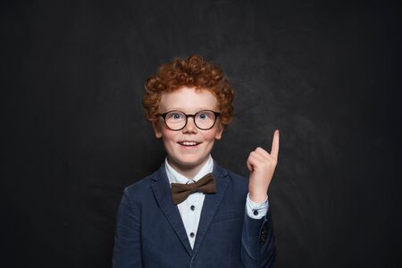 Happy redhead boy pointing up on chalkboard background with copy space