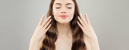 Hübsche Frau mit gepflegten Händen auf grauem Bannerhintergrund. Natürliches Make-up und weißer Nagellack auf den Nägeln