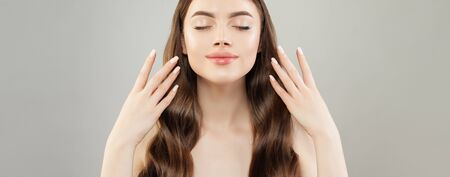 Pretty woman with manicured hands on gray banner background. Natural makeup and white nail polish on nails Standard-Bild