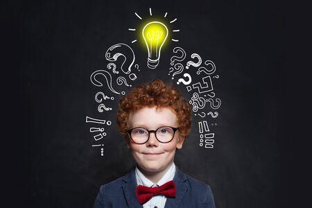 Child and lightbulb on blackboard background