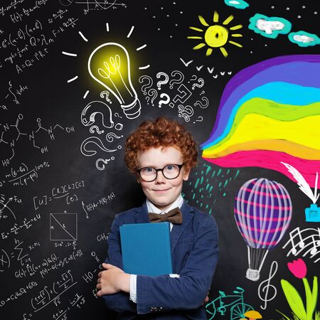 Creativity education. Clever child boy in suit and glasses holding textbook on science and arts occupations pattern background Standard-Bild