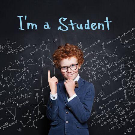 Étudiant intelligent d'enfant dans la salle de classe sur le fond de tableau, concept de retour à l'école