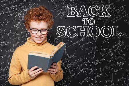 Roodharig kind dat een leerboek op schoolbordachtergrond leest