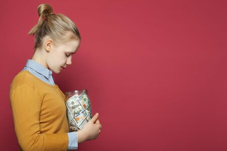 Saving money concept. Pretty young girl holding money cash Banque d'images