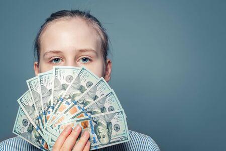 Rich girl holding money cash US dollars on blue background