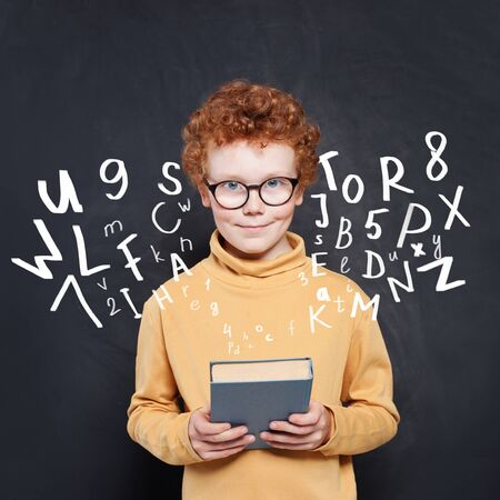 Child boy holding book on chalkboard background with letters and numbers Stock fotó