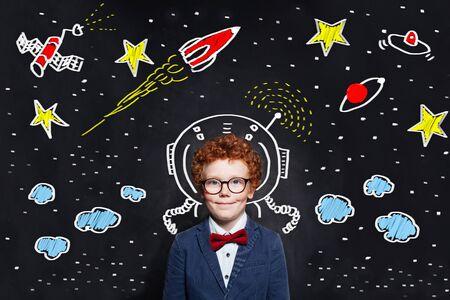 Little boy kid astronaut on blackboard background with space scetch
