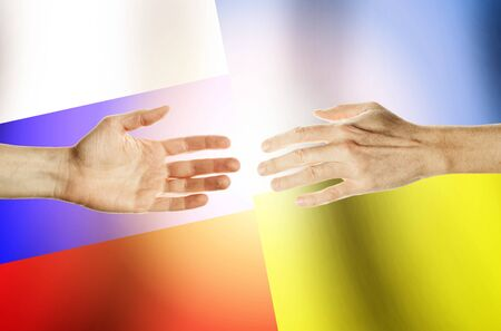 Two hands stretch towards each other against the background. Hands people against the backdrop flags Russia and Ukraine