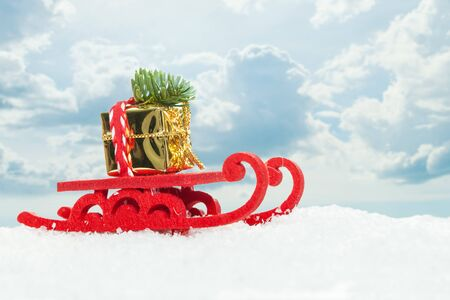 Christmas Santa sleigh with Xmas tree and gold gift on white snow background against sky with clouds. Christmas composition Imagens