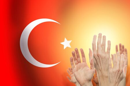 People raising hands and flag Turkey on background. Patriotic concept