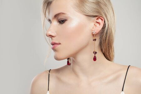 Gold jewelry model. Beautiful woman with fashion golden earrings with red garnet on white background