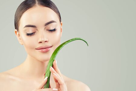 Spa beauty portrait of beautiful young woman with green aloe vera leaf. Skincare and facial treatment concept