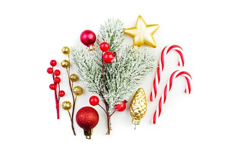 Colorful Christmas decortions. Red baubles, snowy winter holly berries, lollipop and green fir branch on white background