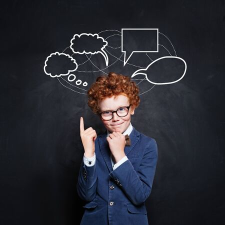 Smart schoolboy pointing at empty speech clouds bubbles on chalkboard background