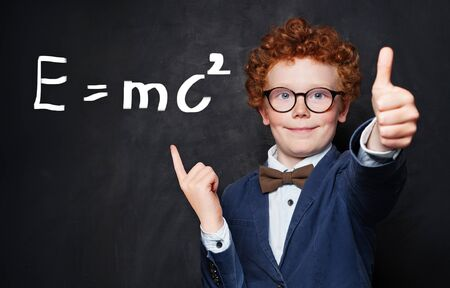 Smiling little boy with ginger hair pointing at science formula on chalkboard background Stock Photo