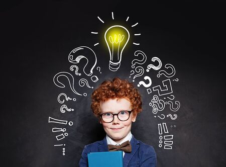 Smart child boy in glasses smiling and holding book on background with lightbulb