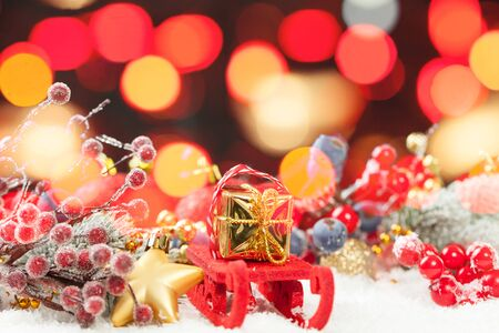 Christmas bokeh background with Santa sleigh, gold gift, red holly berries and colorful Xmas decoration on white winter snow