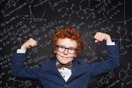 Happy strong child boy on chalkboard background. Back to school concept