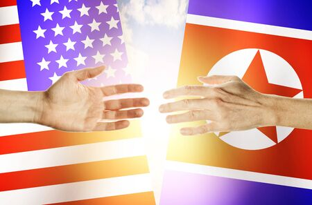 Two hands stretch towards each other against the background. Hands people against the backdrop flags USA and North Korea