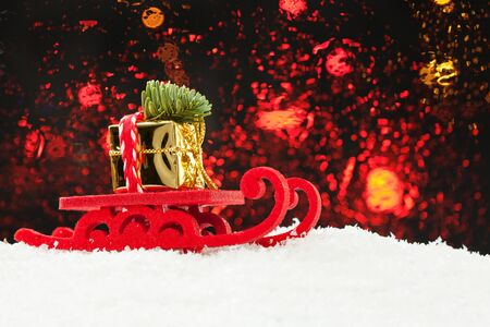 Christmas concept. Santa sleigh driving gold gift and Xmas tree against abstract bokeh light background Stock Photo