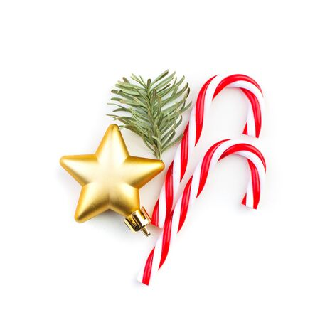 Christmas candy, gold star and green fir branch on white background