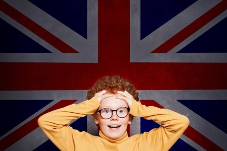 Happy surprised kid with the UK flag background. Learn English language and travel in UK