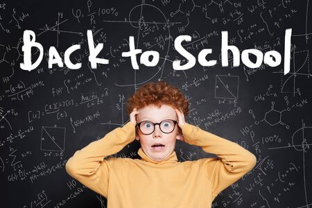 Funny shocked kid against Back to school text. Holidays are over Stock Photo