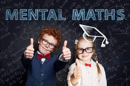 Little successful kids boy and girl student on blackboard background with science and maths formulas. Mental maths concept Reklamní fotografie