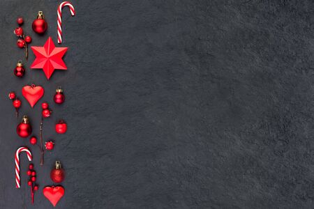 Christmas card on black. Red Christmas decor stars, candy and holly berries flat lay top view on dark background with copy space