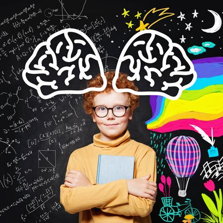 Happy student boy in glasses on blackboard background. Education and school concept