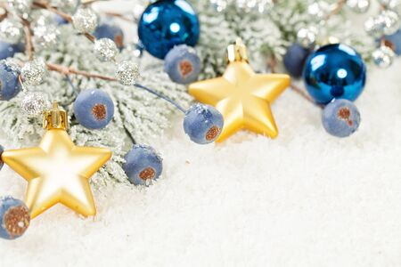 Blue and gold Christmas decoration on white snow background close up Stock Photo