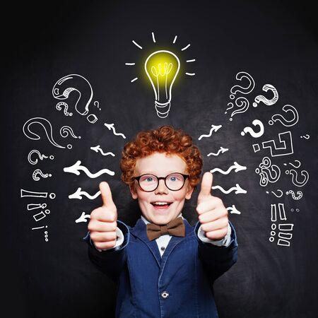 Happy smart child boy in blue suit and  lightbulb Reklamní fotografie