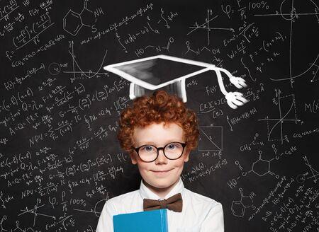 Happy child boy wearing graduation hat on blackboard background with science and maths formulas Reklamní fotografie