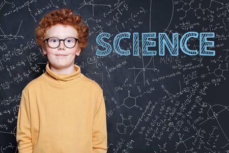 Smart little boy with red ginger hair on science background Reklamní fotografie