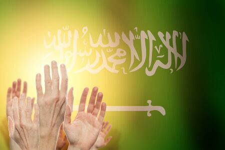 People raising hands and flag Saudi Arabia on background. Patriotic concept