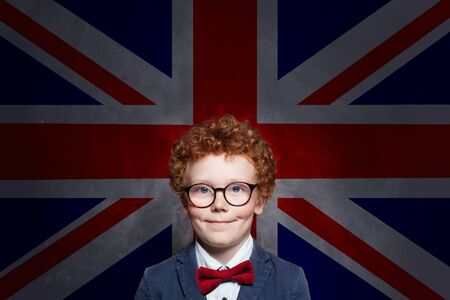 Happy cute kid boy in glasses with the UK flag background. English concept