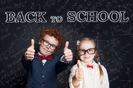 Successful clever children in school uniform showing thumb up on blackboard background, back to school and science power concept