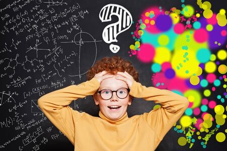 Kid with question marks on background with science and arts scetch Reklamní fotografie