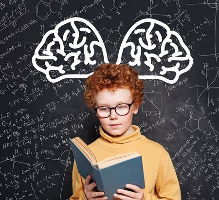 Smart child student wearing glasses holding book and learning science