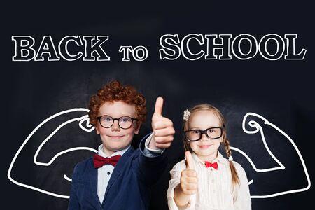 Successful smart kids in school uniform having fun on blackboard background, back to school and brain power concept