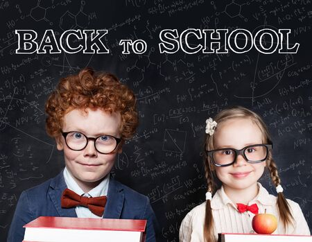 Smart kids wearing glasses holding books and smiling. Back to school concept